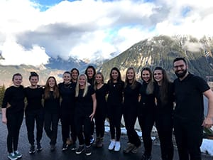 group of 13 young men and women in smart black uniforms against an alpine mountain backdrop